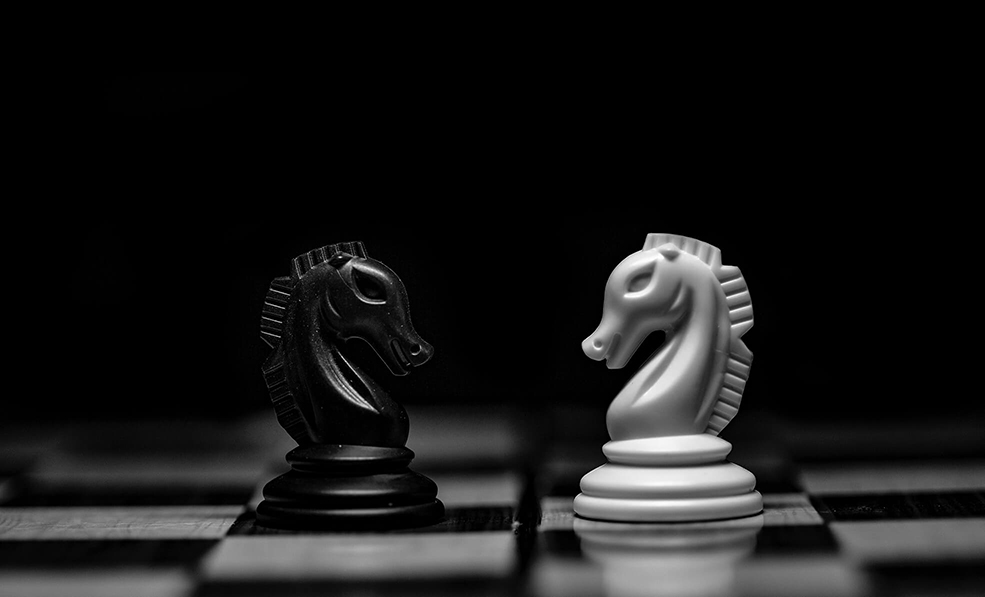 An image of black and white chess pieces turned towards each other on a chess board.