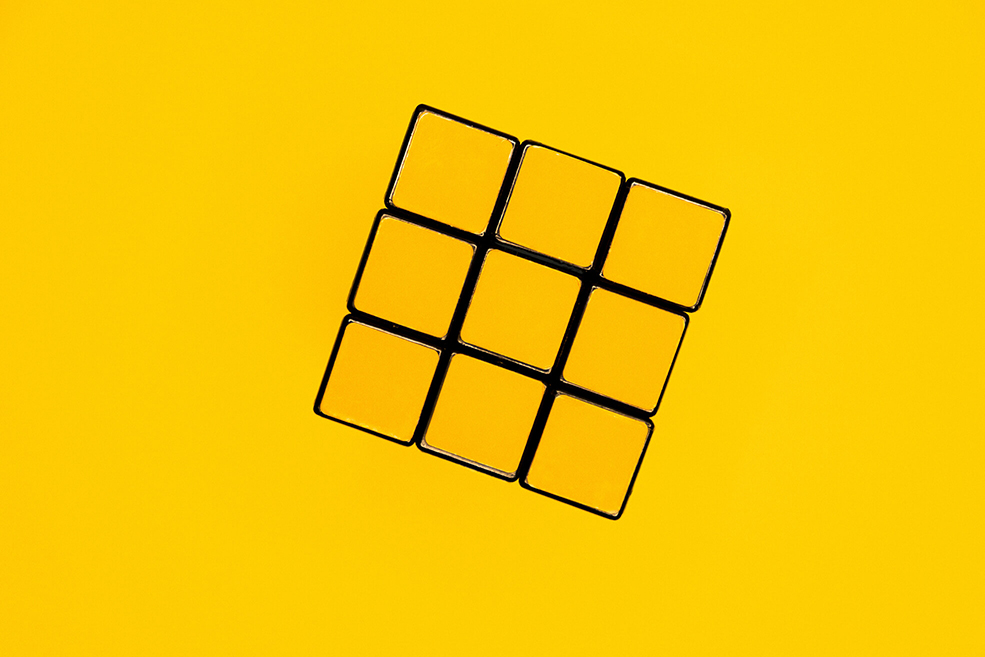 An image showing a yellow Rubik cube on a yellow background.